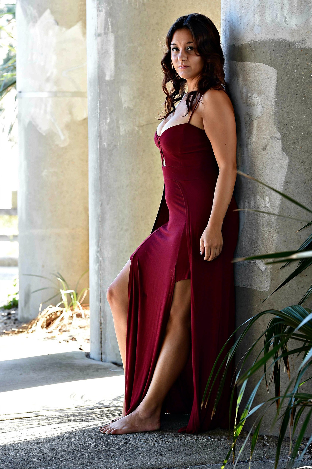 A style blogger wears a maroon maxi dress with side slits.
