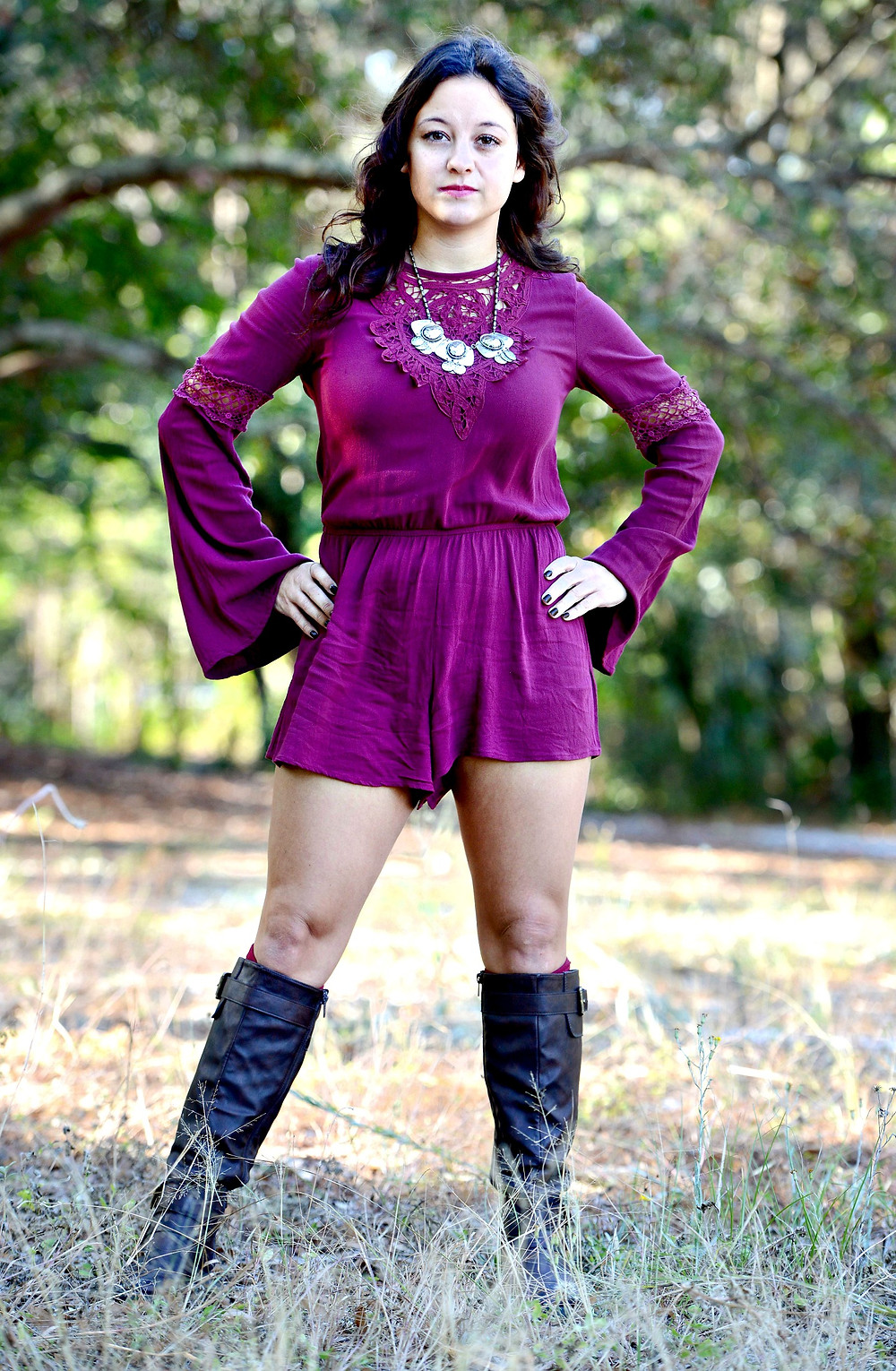A fashion blogger wears a long-sleeve, burgundy romper with bell sleeves paired with a chunky necklace and boots.