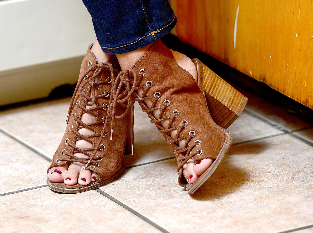 A style blogger wears tan, suede lace-up heels.