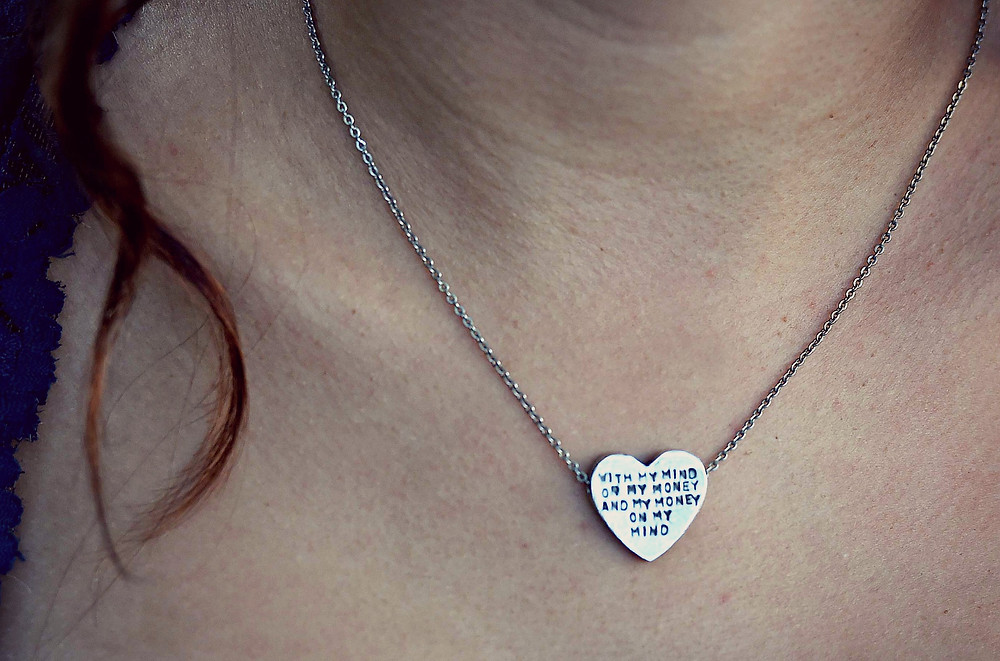 "A fashion blogger wears a heart necklace featuring ""Gin and Juice"" lyrics by Snoop Dogg."