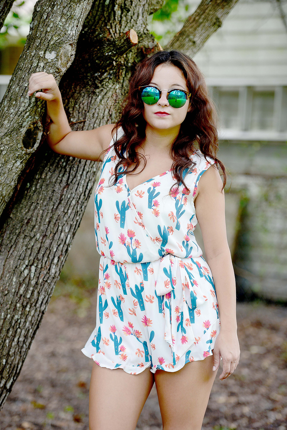 A fashion blogger wears a cactus flower romper with ruffles and sunglasses.