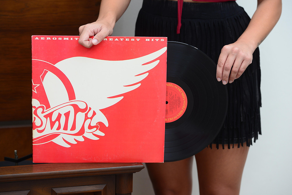 """A music blogger pulls out the vinyl record """"Aerosmith's Greatest Hits"""" by Aerosmith."""