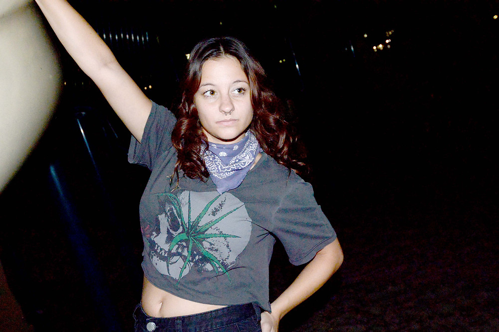 A fashion blogger wears a skull crop top and purple bandana.