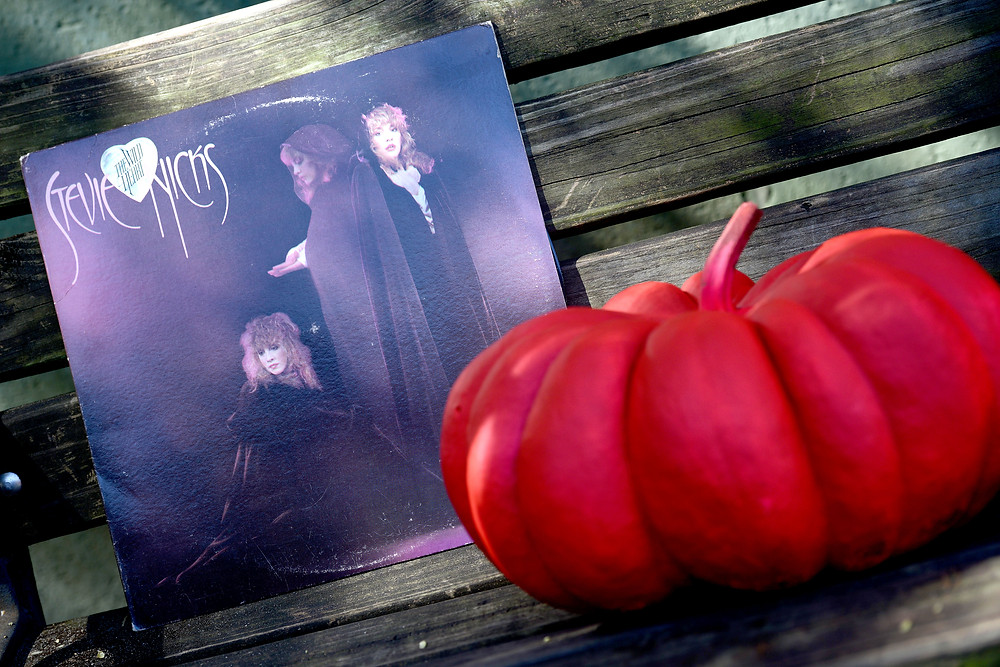 """The """"Wild Heart"""" vinyl record by Stevie Nicks sits on a bench next to a hot pink pumpkin."""
