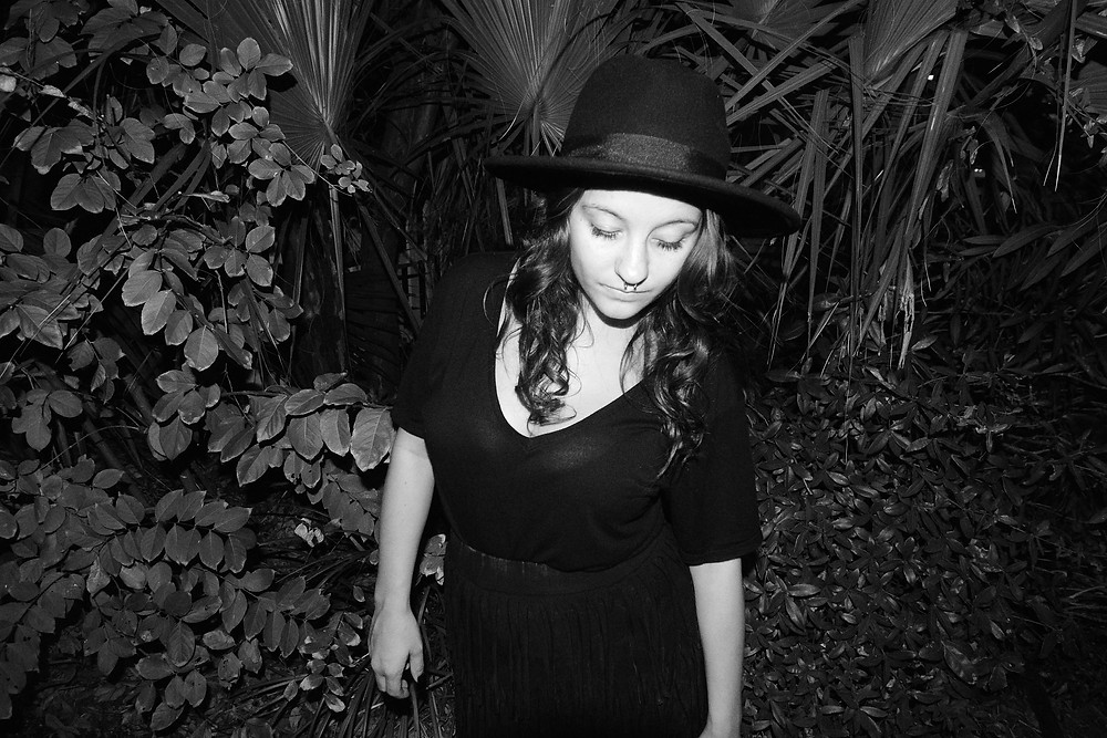 A fashion blogger wears a medium-brim fedora over her curled hair.