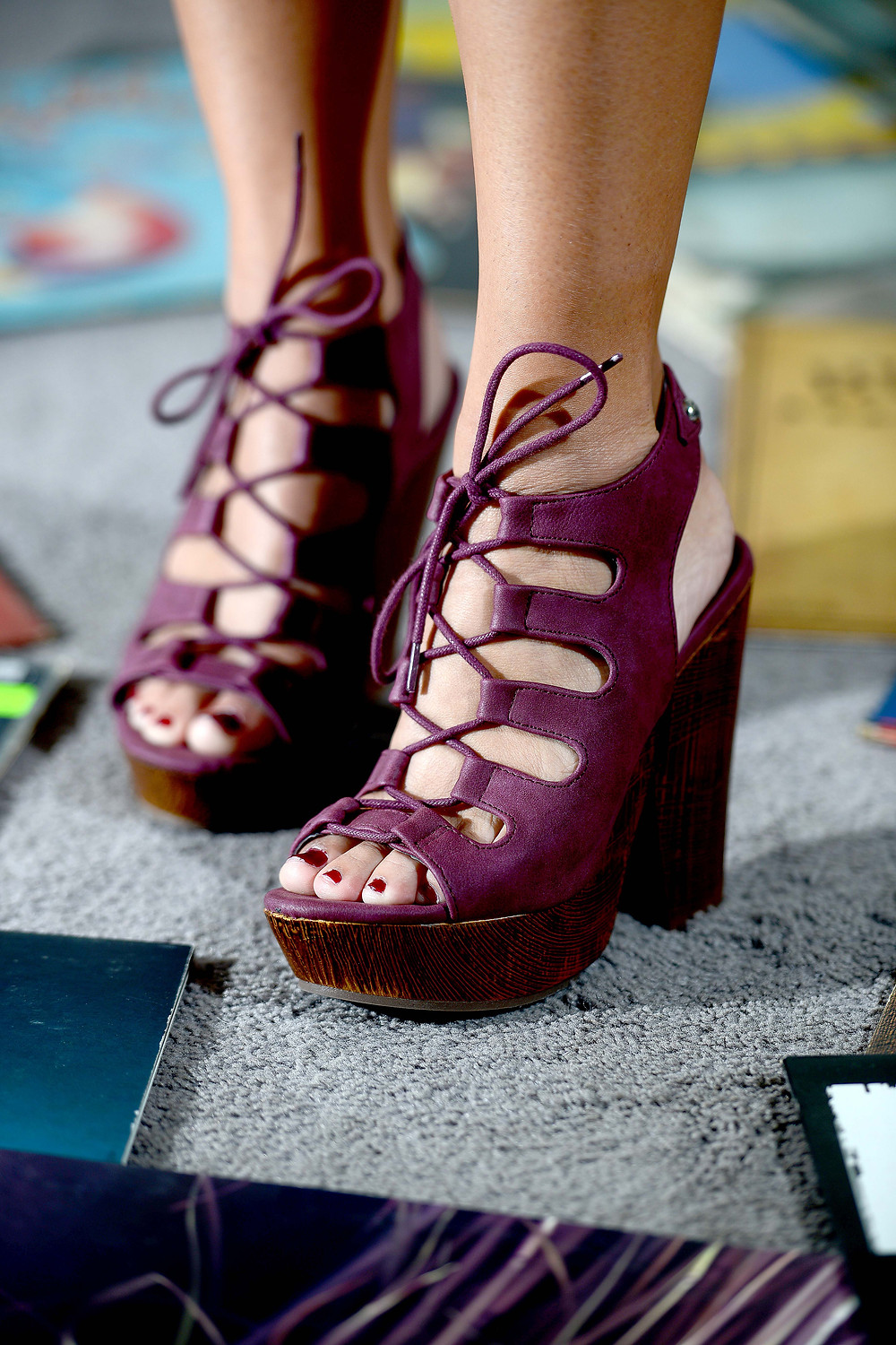 A music blogger and vinyl record collector poses in purple, lace-up heels with a section from her vinyl record collection.