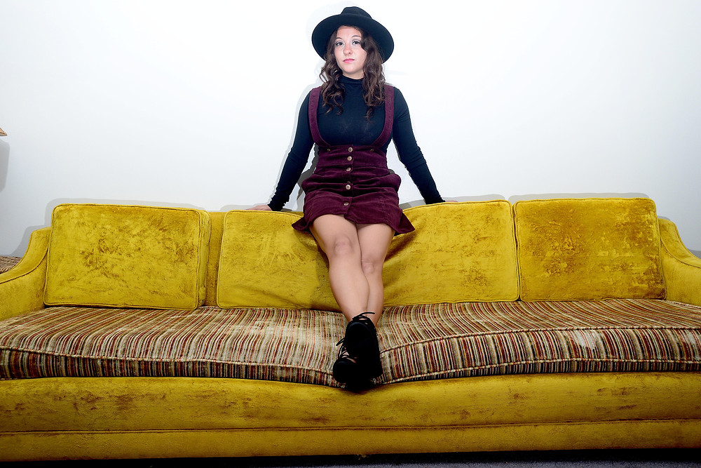 A fashion blogger stands in a black turtleneck, corduroy suspender skirt and black, lace-up heels.