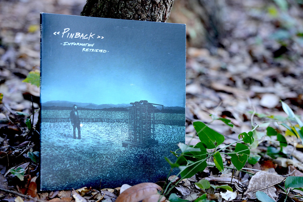 """Information Retrieved"" vinyl record by Pinback sits in fall leaves."
