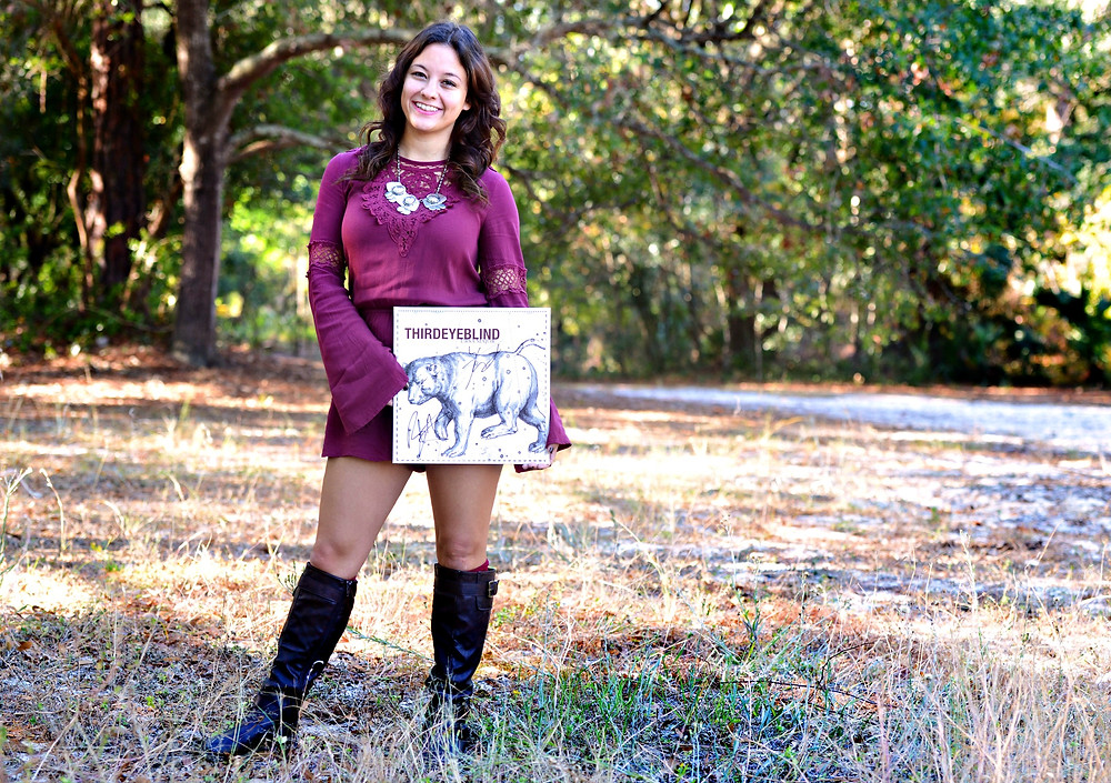 """A music blogger holds up the """"Ursa Major"""" vinyl record by Third Eye Blind."""