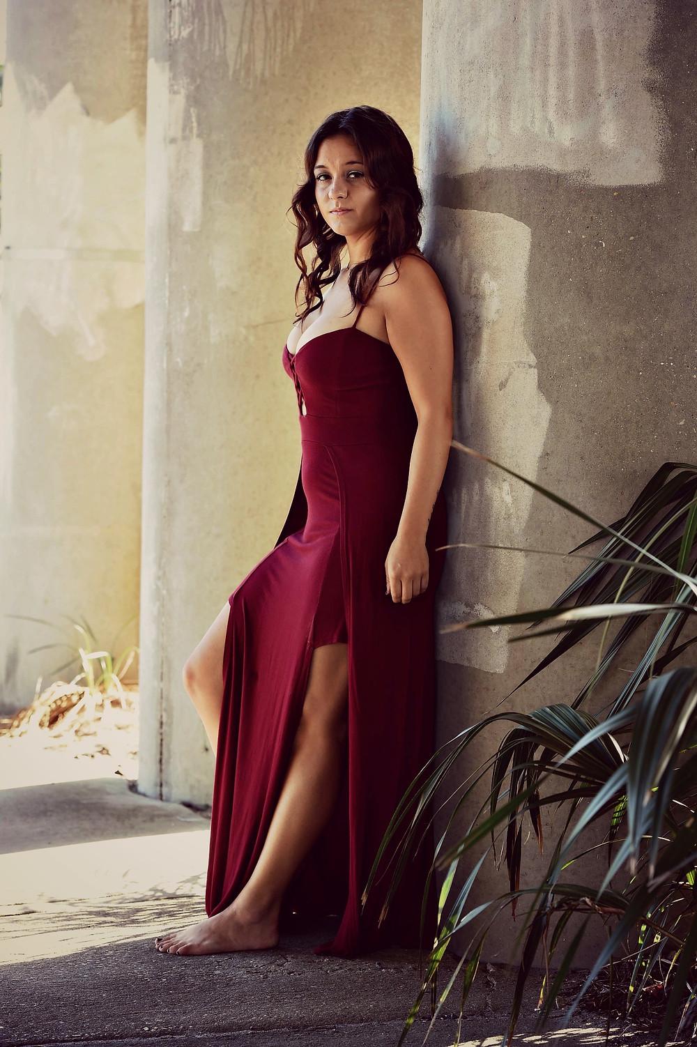 A fashion blogger wears an oxblood maxi dress with a side slit.