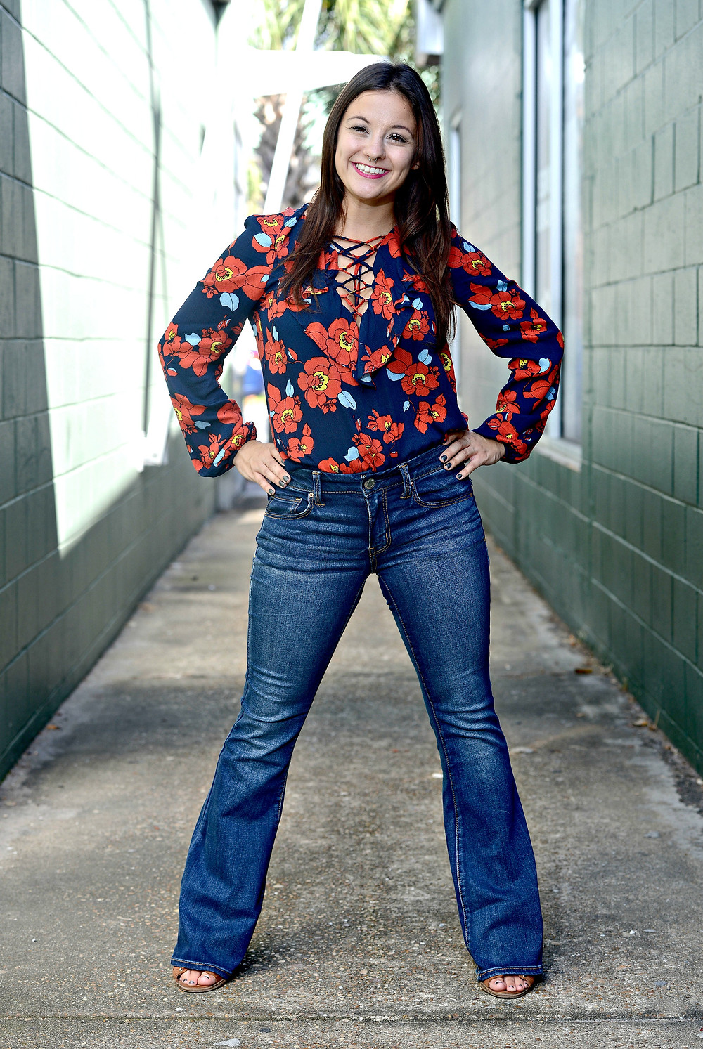 A style blogger wears a floral lace-up blouse and flared jeans.