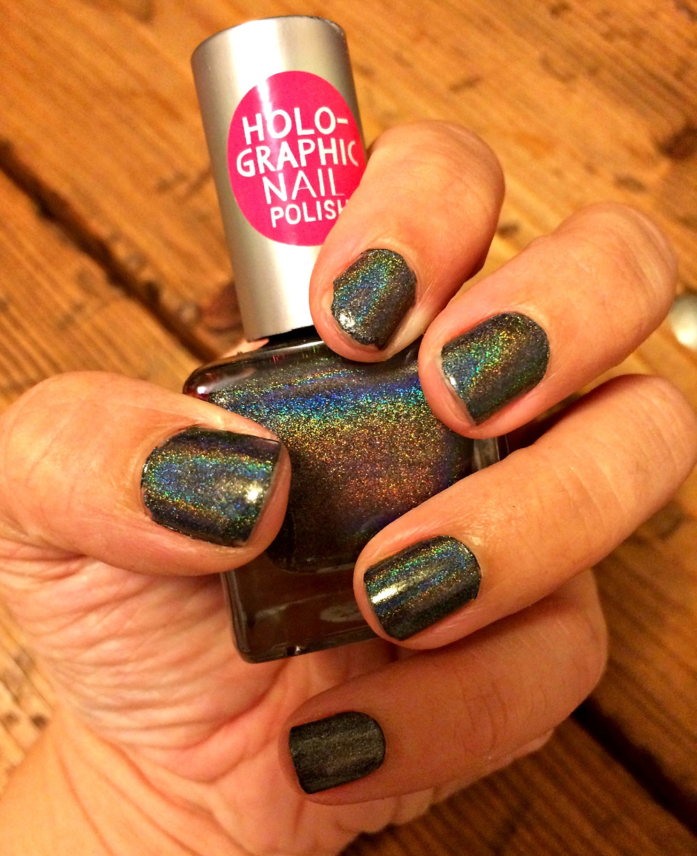 A beauty blogger wears Urban Outfitters holographic nail polish in black.