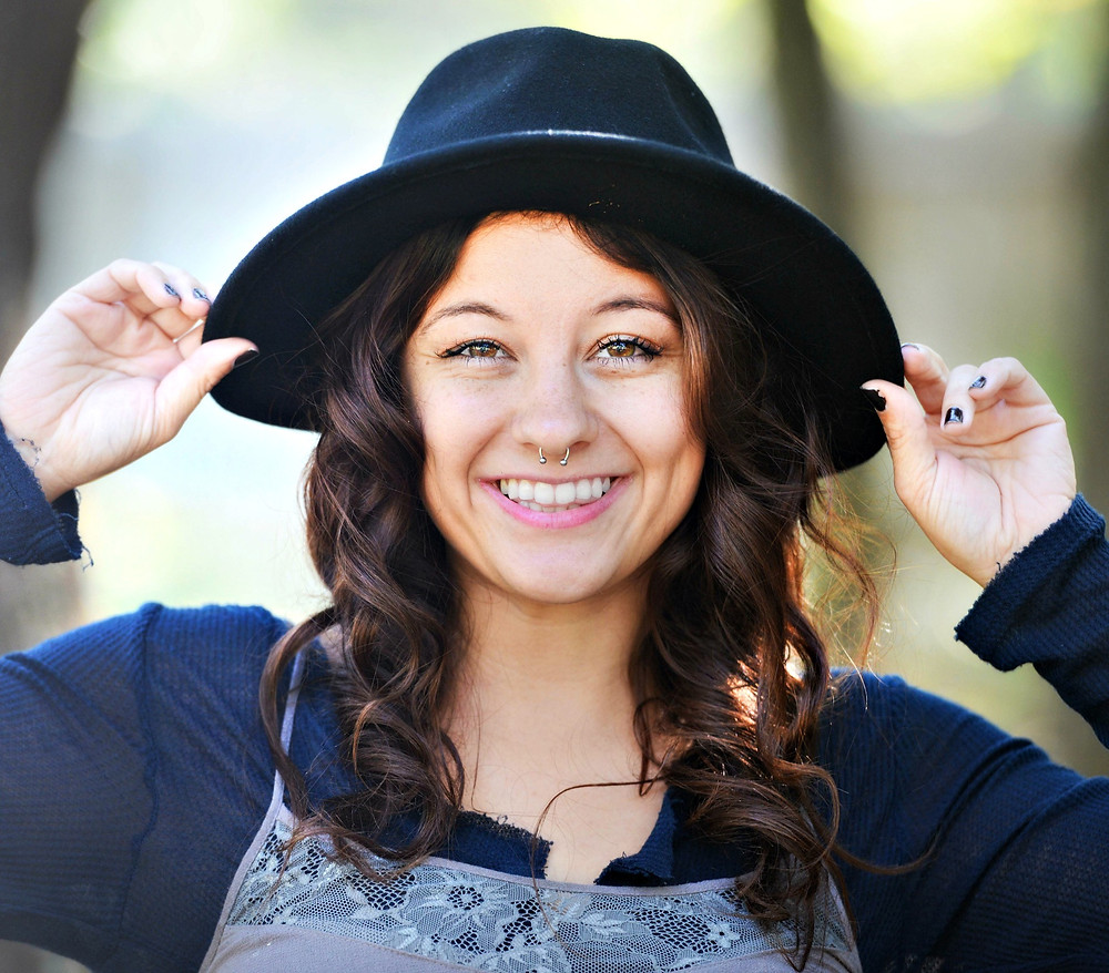 A style blogger puts on a medium-brim, black fedora.