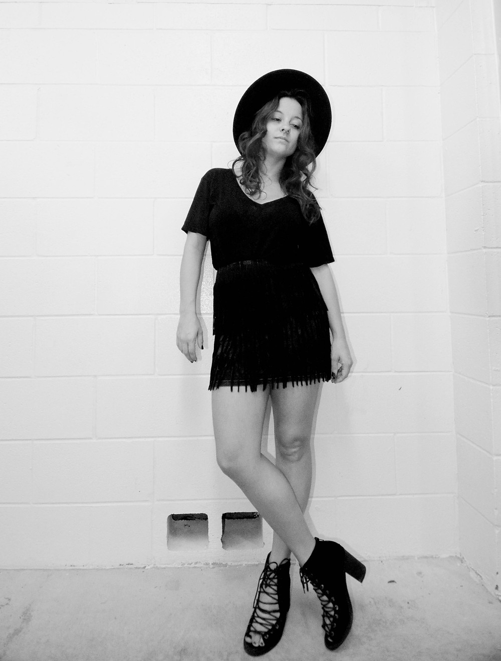 A style blogger wears a black fringe skirt with a black T-shirt and medium-brim fedora.