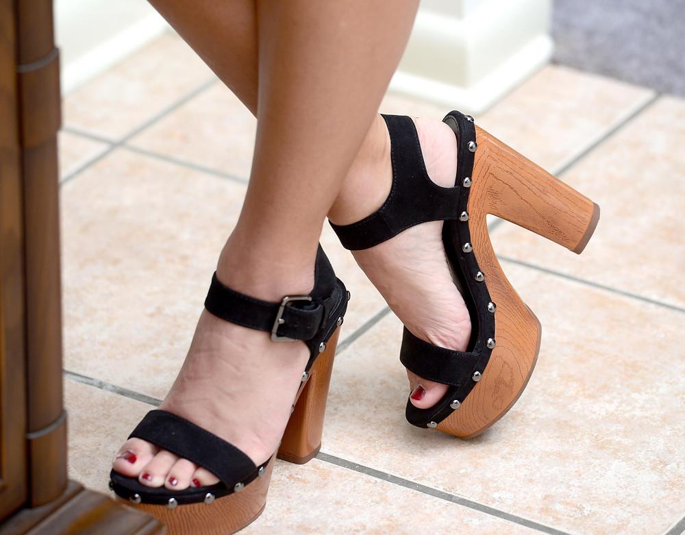 A fashion blogger wears black platform heels.
