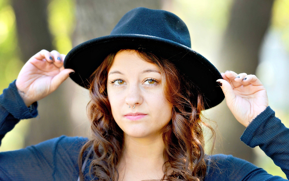 A fashion blogger puts on a black, medium-brim fedora.