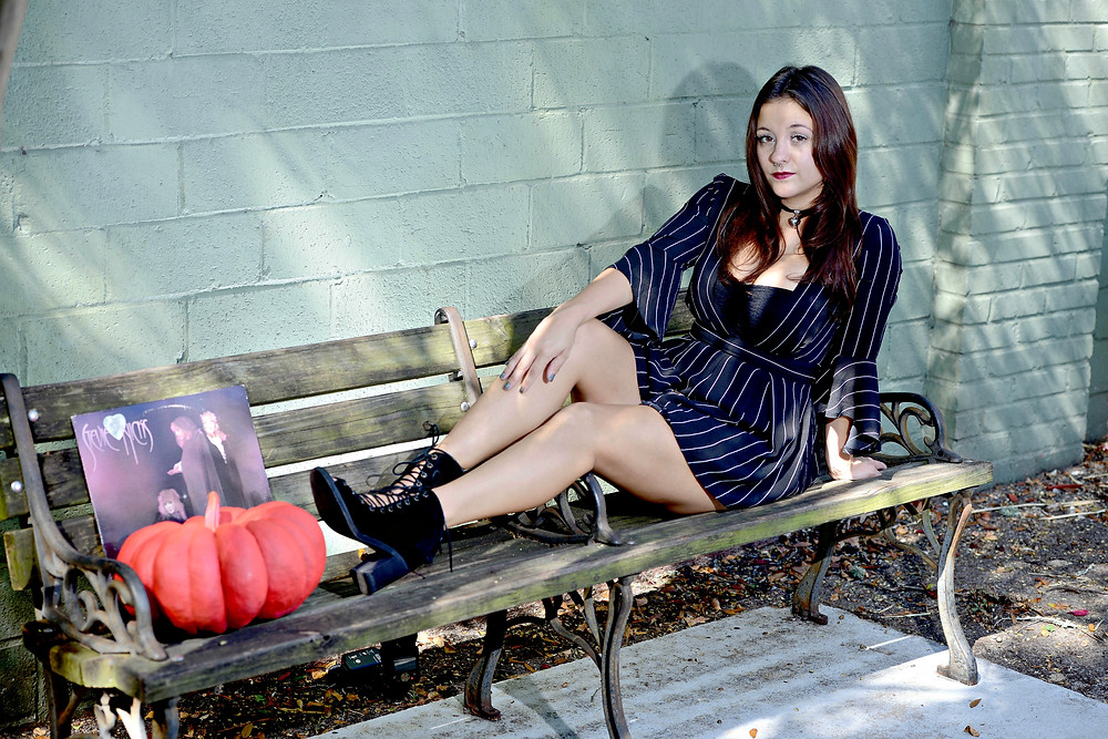 """A fashion blogger poses on a bench next to a hot pink pumpkin and the """"Wild Heart"""" vinyl record by Stevie Nicks."""