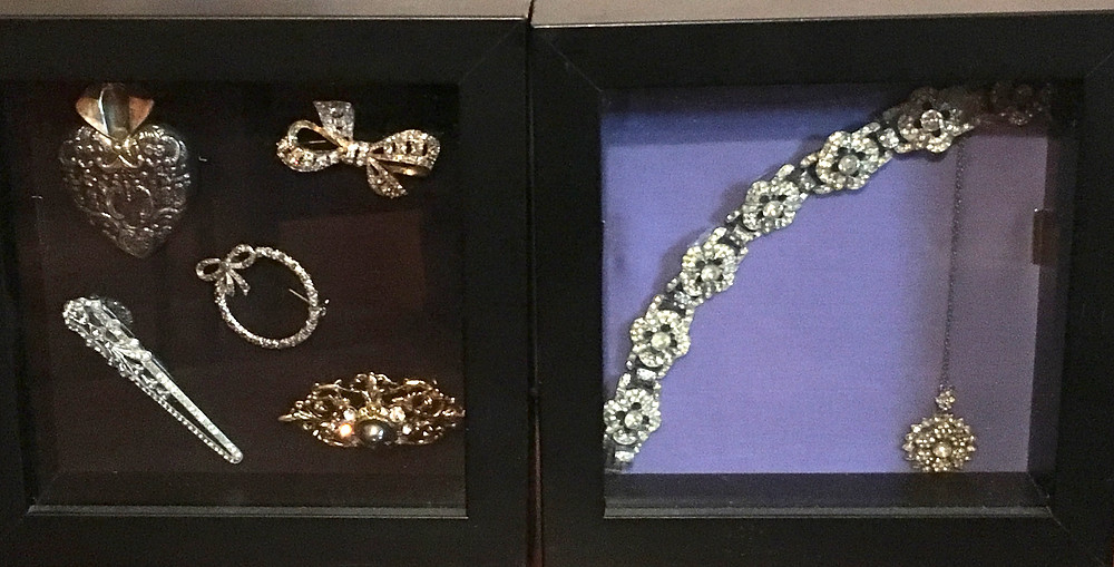 Heirloom jewellery in recessed picture frames.