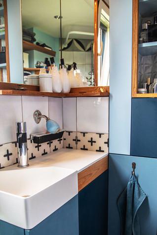 Espace lavabo avec miroirs de coin pour agrandir l'espace et tablette en châtaignier
