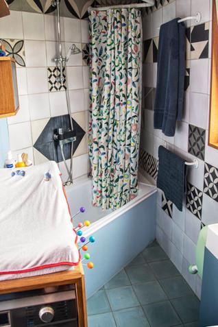 La salle de bain, petite, compacte et complète: une baignoire pour les enfants, qui sert de douche aux parents, une table à langer au-dessus de la machine à laver.
