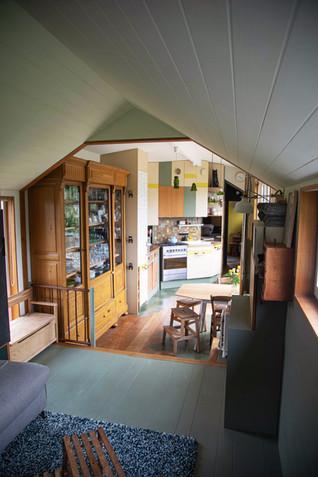 Vue du salon sur toute la perspective et longueur de la tiny. On voit les deux hauteurs de toits, avec le toit double pente du salon moins haut qui donne une sensation nid/cocon dans le salon.