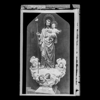 San José con Niño en brazos sobre nube con querubines