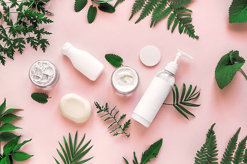 Natural cosmetics and green leaves on pink background, top view, flat lay. Natural organic