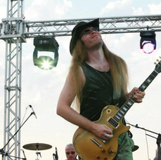 Les Paul Gold Bullion being played by Howie G, wearing a hat on an open air stage in Lindos, Rhodes