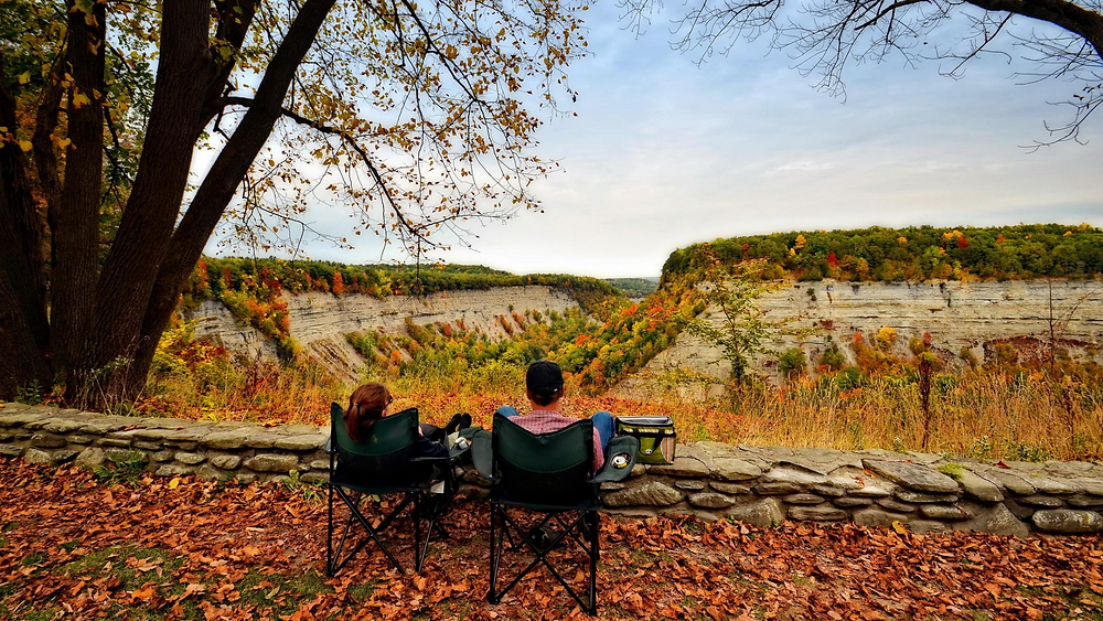 two people sitting in chairs facing a gorgeous fall view in Letchworth State Park