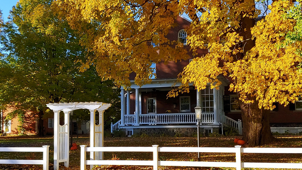 BrickInn side view of Fall trees and porch of house with trellis