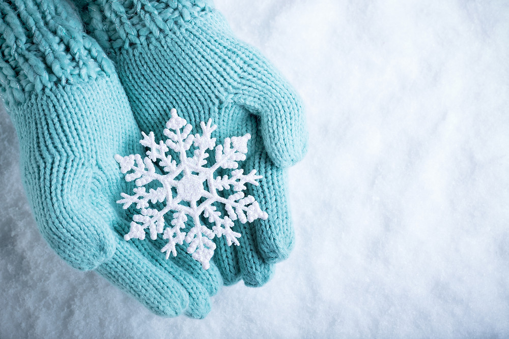 Female hands in light teal knitted mittens with sparkling wonderful snowflake on
