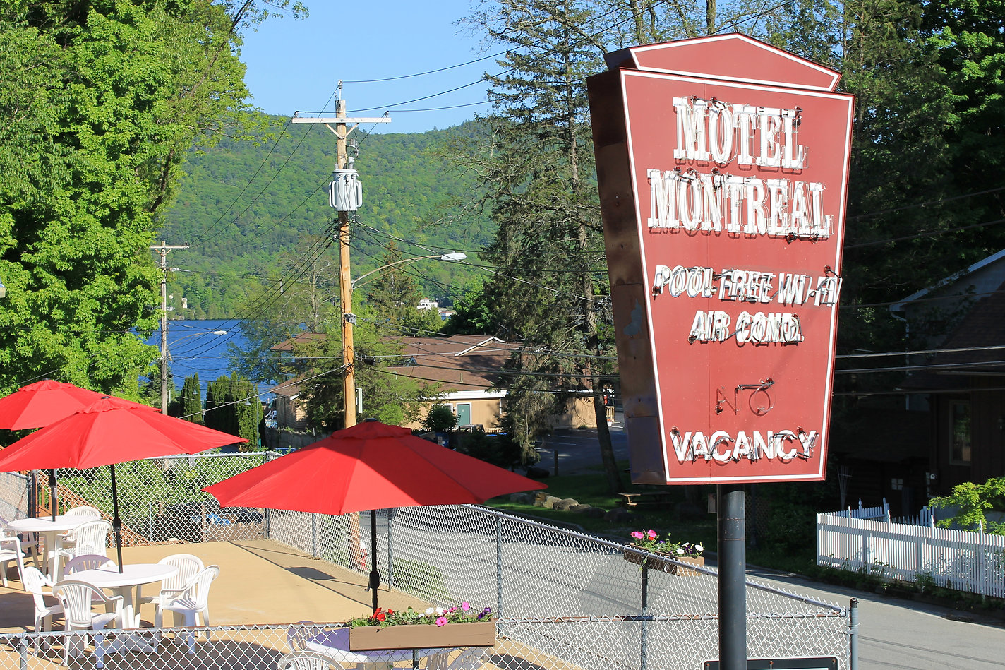 Lake George Motel Montreal neon sign and sundeck with red umbrellas and Lake George views
