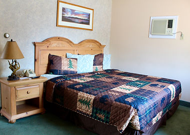hotel room with a queen size bed and rustic adirondack themed bedspread and curtains at the lake haven motel in lake george, ny