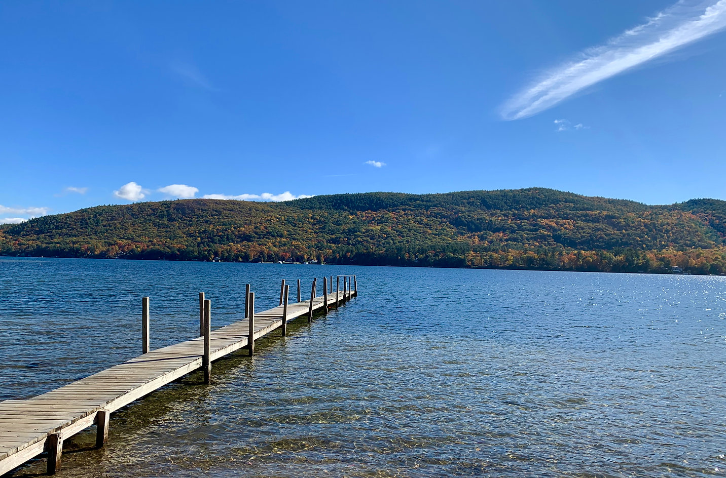 wooden dock stretching out over the waters of lake george with a deep blue sky and the adirondack mountains in the background