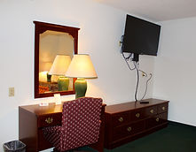 work station and wall mounted television in  king room at the sundowner motel