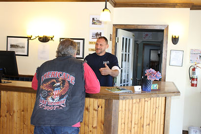 sundowner on lake george front desk staff speaking with hotel guest wearing an Americade motorcycle rally vesst