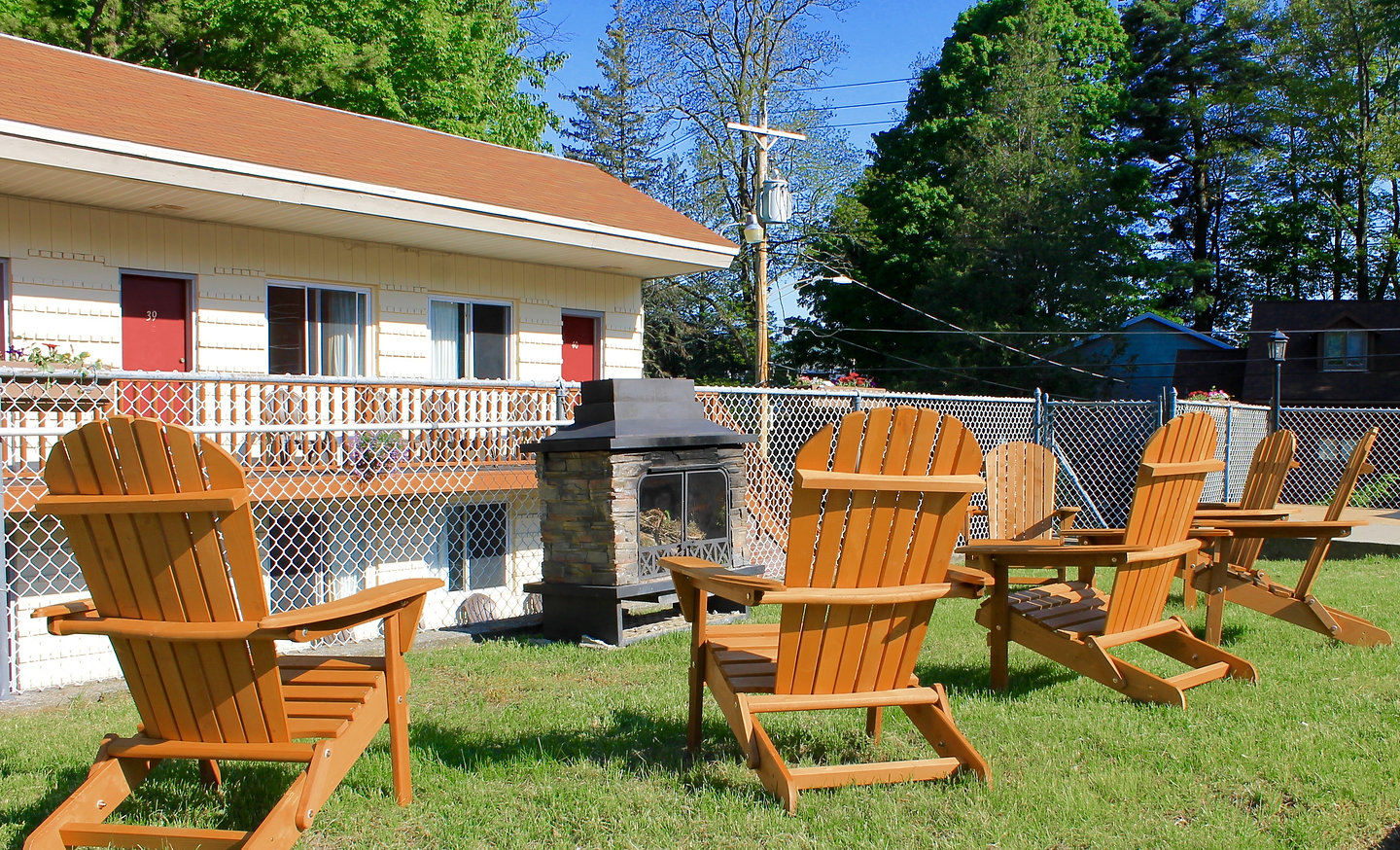 Outdoor fireplace surrounded by Adirondack chairs with the Lake George Motel Montreal in the background
