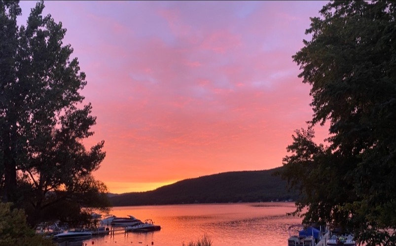 purple and pink skies reflecting over the waters of lake george at sunrise with adirondack mountains in the background