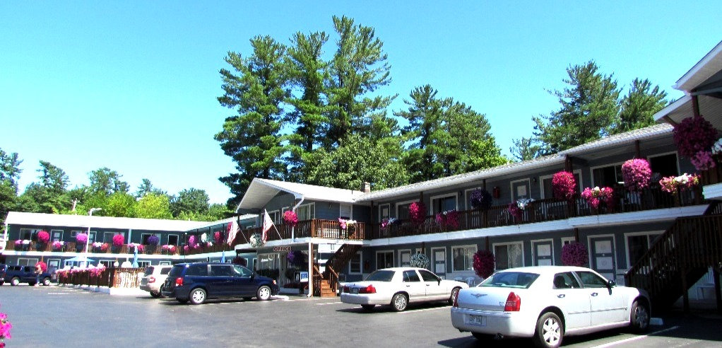 lake haven motel in lake george new york with purposle and pink flowers handing from the balcony and pool and a blue sky in the background