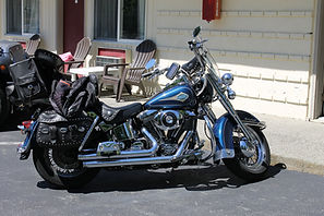 Blue Harley Davidson motorcycle parked in front of a hotel room at the Lake George Motel Montreal