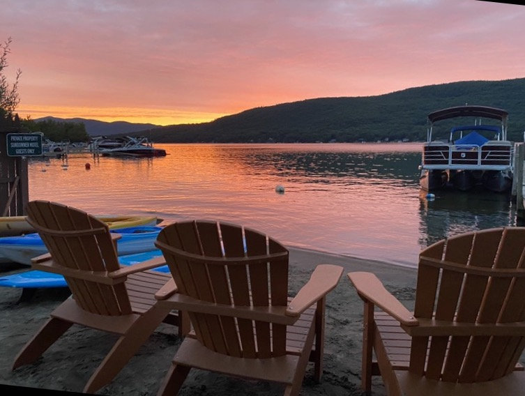 three adirondack chairs and the waters of lake geroge at dusk with the adirondack mountains in the background
