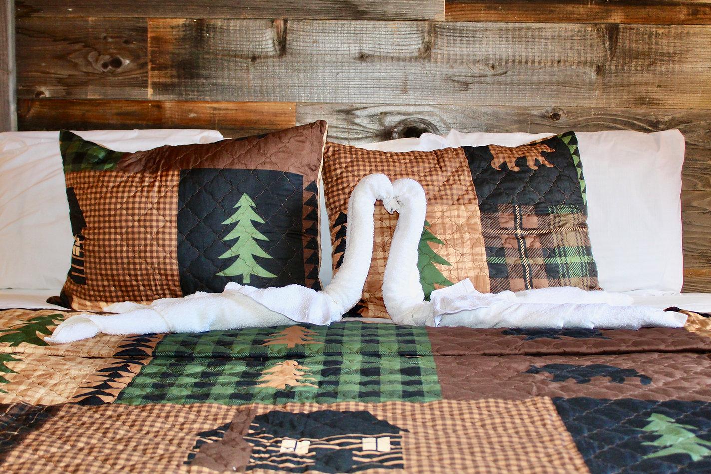 handmade barnwood headboard with rustic bedding and swan shaped towel sculpture at the sundowner on lake george