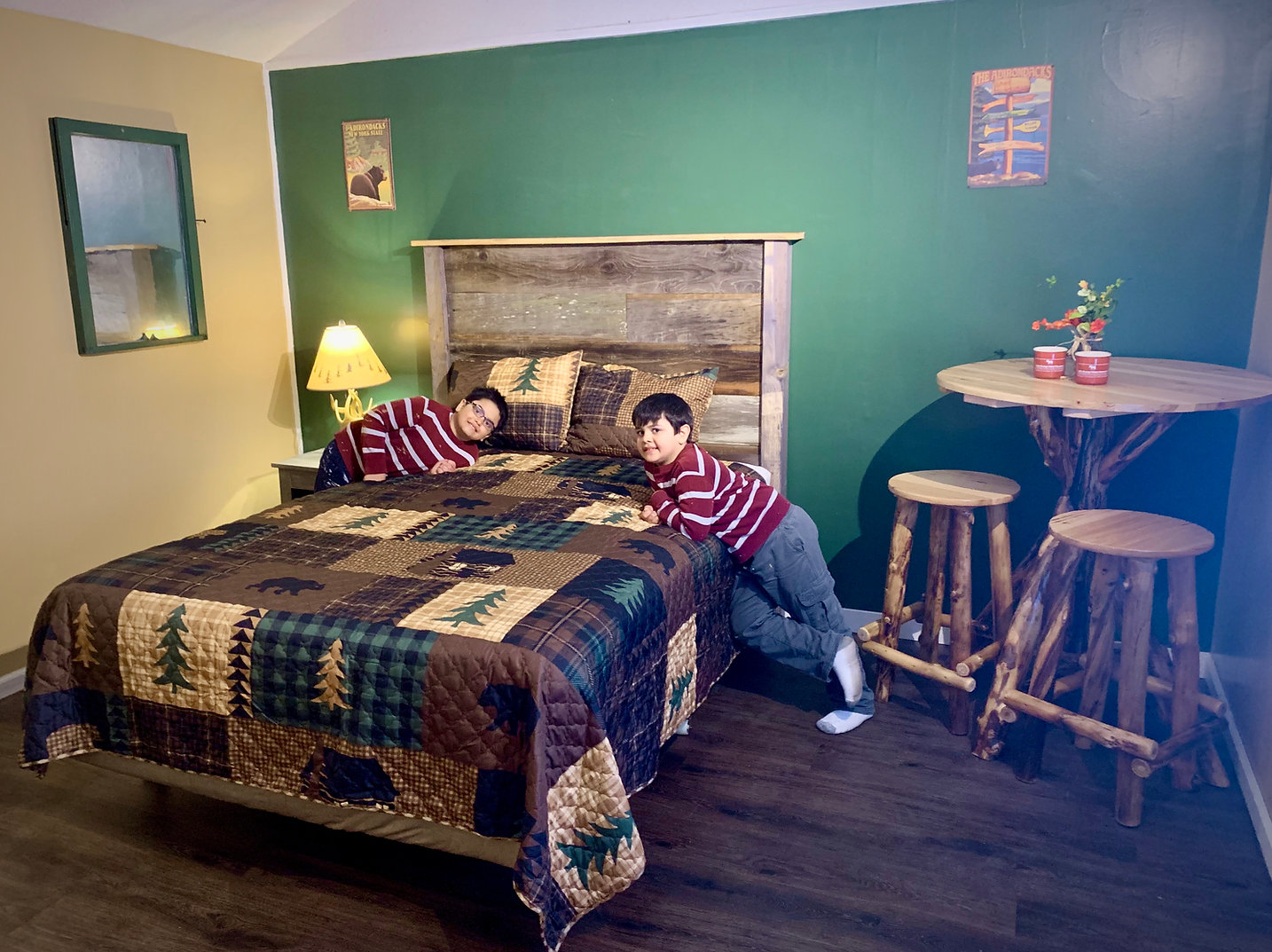 two school age boys leaning on a bed with a adirondack style comforter and handmade reclaimed wood head board in background and aspen wood table and stools and rustic decor in a newly renovated kitchentte studio at the lake george motel montreal in lake george ny