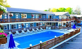 deep blue water of the swimming pool at the lake haven motel and the blue exterior of the lake haven motel in lake george ny