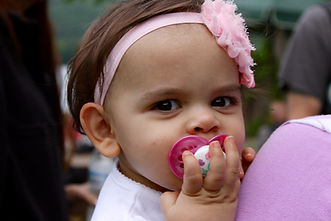 Baby girl with a pacifier in her mouth and pink bow on her head