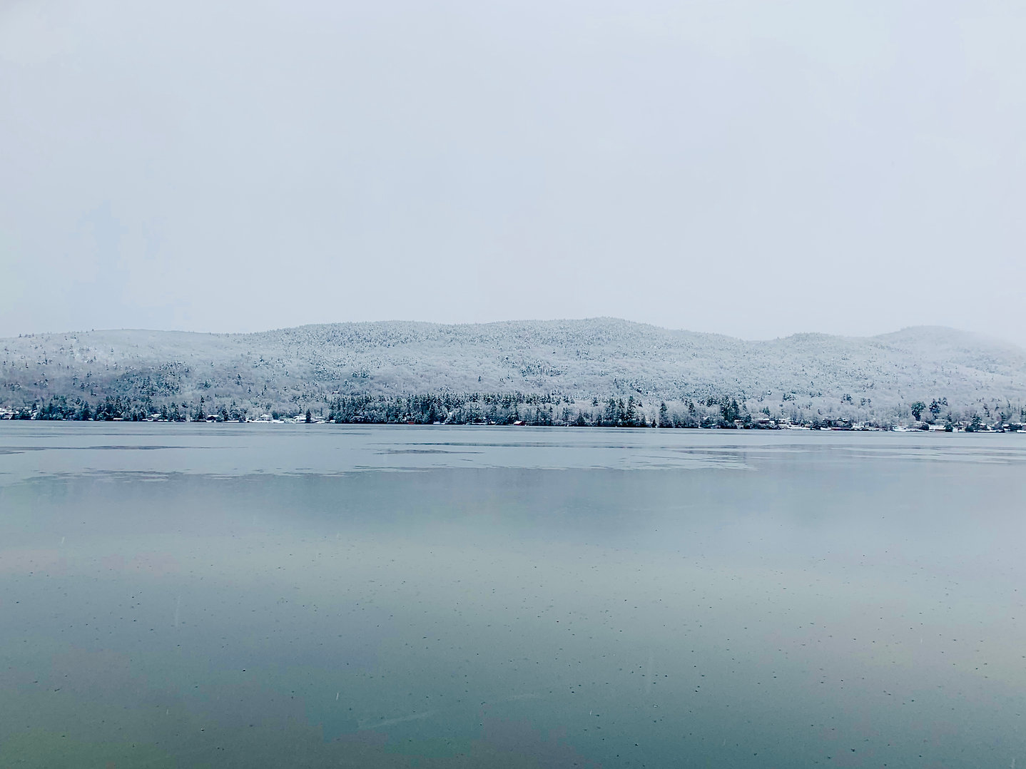 Lake George on a chilly winter morning with snow covered Adirondack mountains in the distance