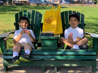 two little boys sitting in adirondack chairs eating a cookies with a Lake George Baking Company bag in between them