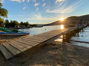 dock and beach that the sundowner on lake george with two kayaks and the sun rising over the lake george water and adirondack mountains