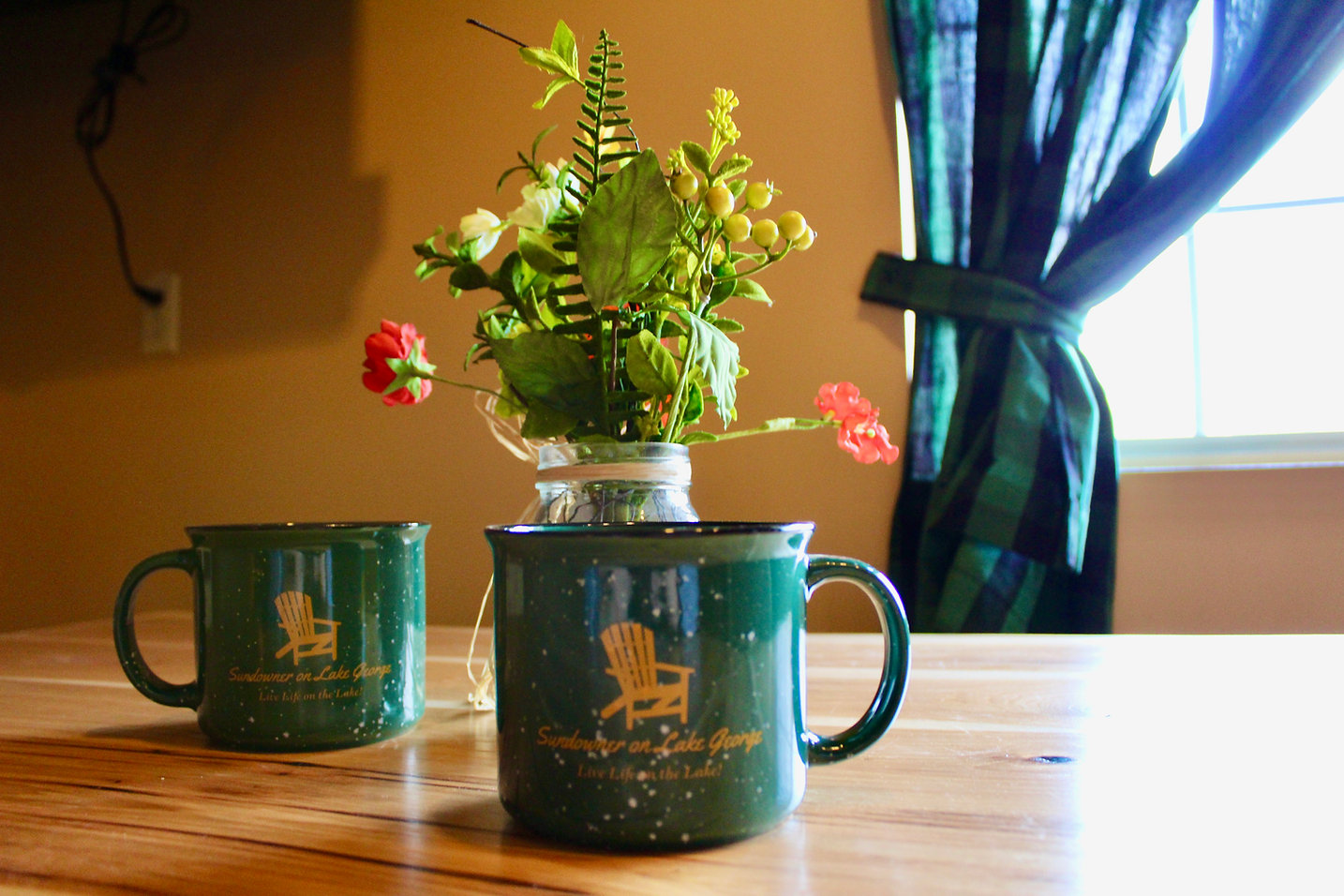 sundowner on lake george campfire coffee mugs with fresh flowers in the background