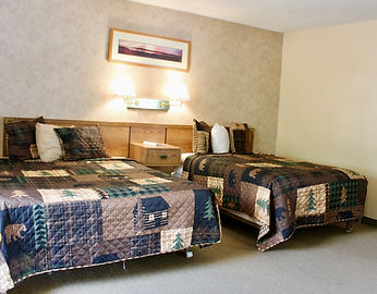 hotel room with two beds and dirondaack themed decor at the lake haven motel in lake george ny